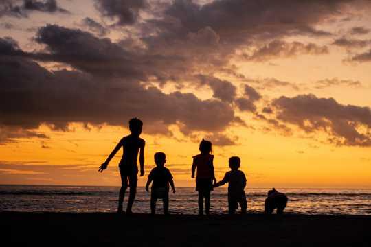 黄昏时沙滩上孩子剪影图片