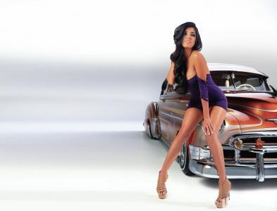女孩,美丽的女孩,黑发,在一件衣服,坐在一辆旧车的翅膀,看着相机,在浅色背景