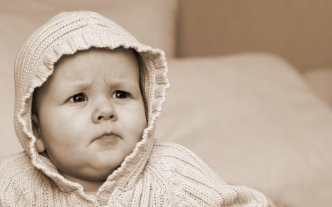 一个严重的婴儿,一件罩衫针织外套,额头皱纹