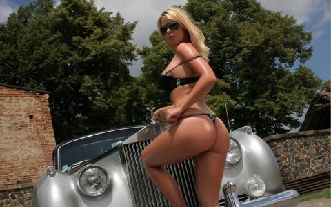 女孩,美丽的女孩,金发,戴着眼镜,站在一辆旧车旁边,看着相机,脚在保险杠上