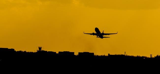 夕阳下呼啸而过的飞机