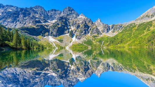 阿尔卑斯山,湖面光滑,绿树环绕,倒影